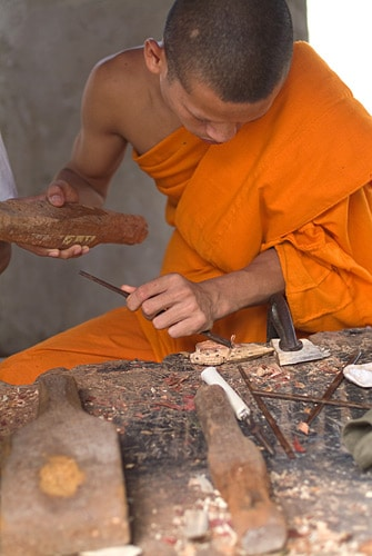 Monje tallando imágenes de Buda sobre madera