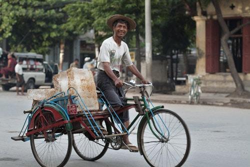 Alegre conductor cargando bloques de hielo en Mandalay