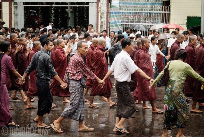 Birmanos con las manos unidas protegiendo a los monjes