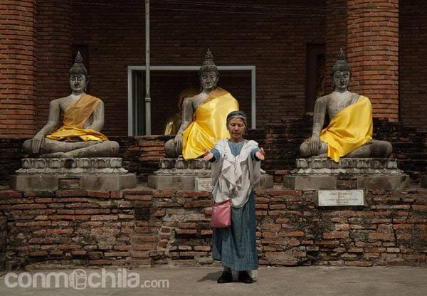 Señora haciendo sus plegarias frente a los budas de detrás del monasterio