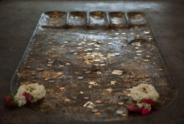 Detalle de la huella de Buda con monedas y pan de oro