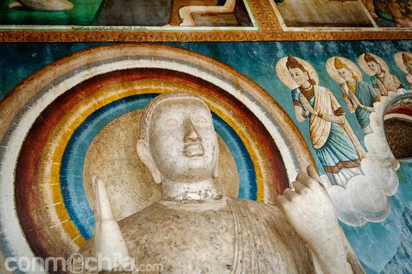 Una imagen de Buda en un pequeño templo al lado de la stupa