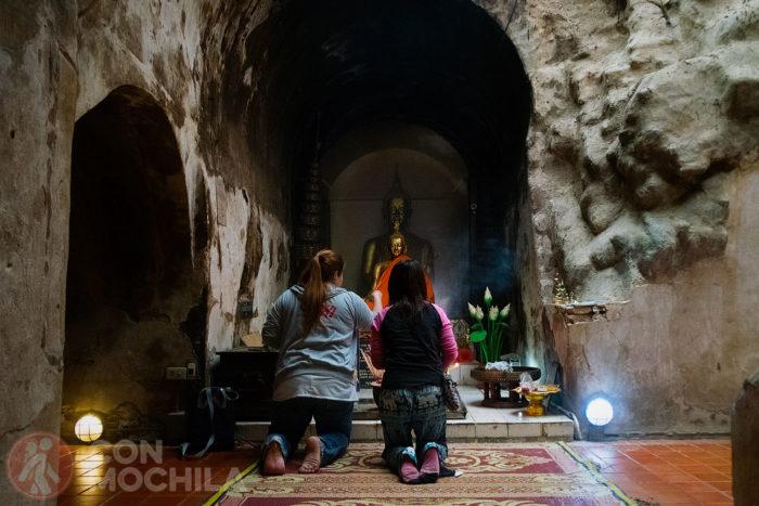 Devotos rezando ante una imagen de Buda