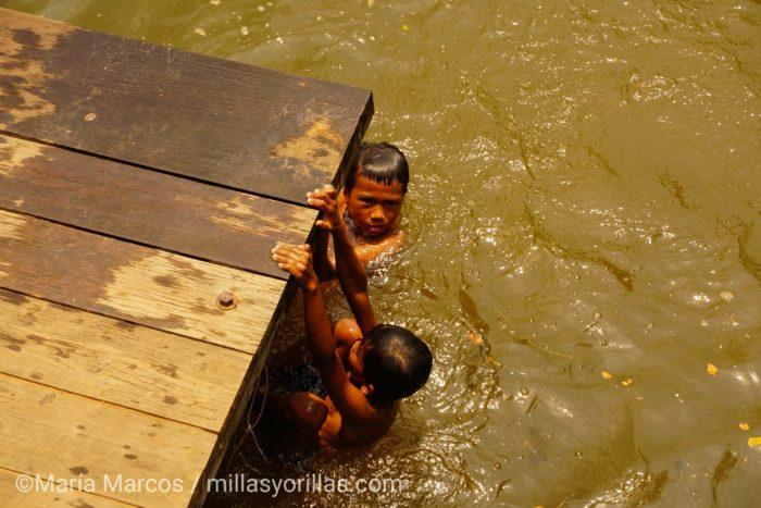 Niños camboianos dandose un baño mientras sus padres venden a los turistas.